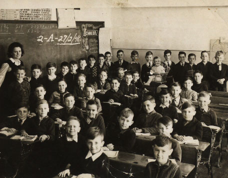 An old fashioned school room with teacher and class